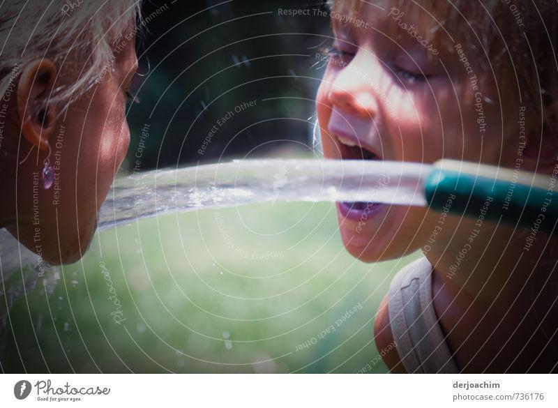 two Quench. Zwei Girls trinken Wasser aus dem heraus strömenden Wasserschlauch. Eins links das andere rechts. Freude Gesundheit Leben Mädchen Kopf Mund 2 Mensch