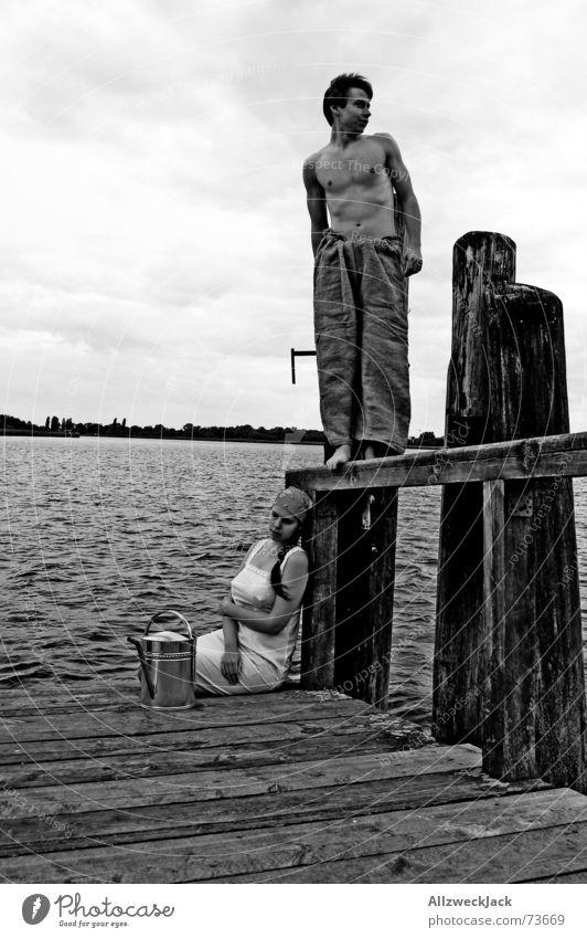 Hans guck in die Luft unverstanden Steg Holz Mann Frau schwarz schlechtes Wetter Wolken Partnerschaft Aussicht Außenaufnahme Wasser holen Gießkanne