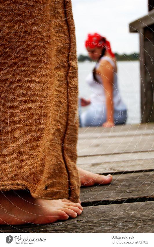 Hans macht sich an Grete ran Frau Mann Wasser rot Holz Fuß braun Seil Hose Steg Barfuß Kopftuch imitieren