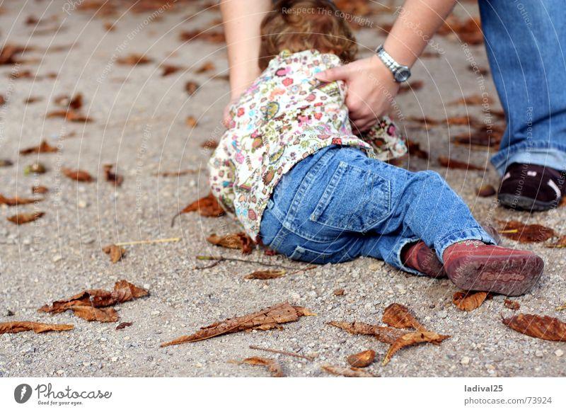 hingeplumst Farbfoto Außenaufnahme Tag Ganzkörperaufnahme Rückansicht Kind Beine Fuß Hose Schuhe Locken fallen heben Bodenbelag