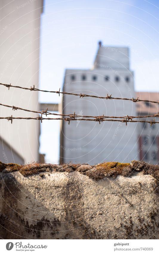 Begrenzte Freiheit Stadtrand Haus Industrieanlage Mauer Wand Fassade Stacheldraht Stacheldrahtzaun bedrohlich Angst Misstrauen Frieden Krieg Macht