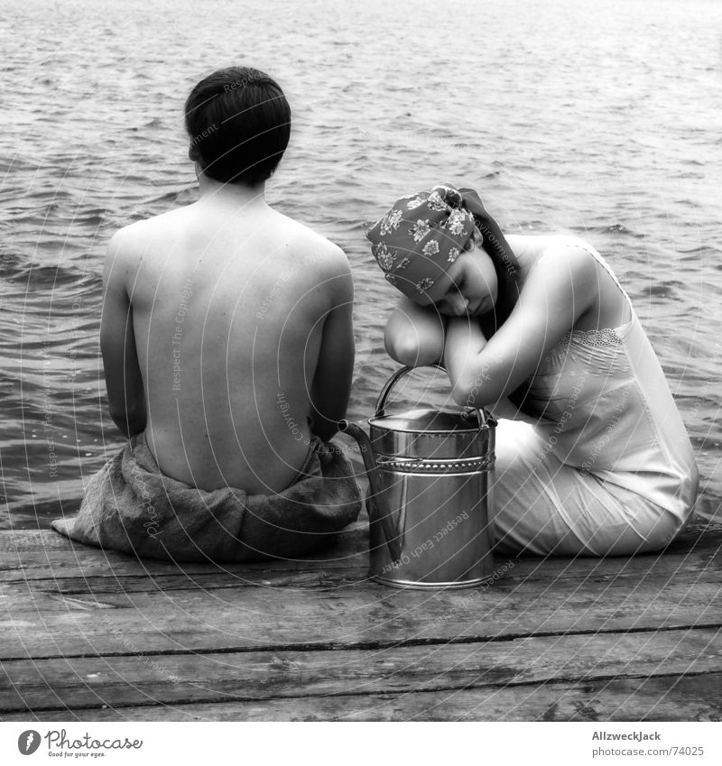 Grete träumt vom Traummann Frau Mann Wasser Holz Küste sitzen trist Hose Steg Langeweile Kopftuch Gießkanne Kannen Wasser holen