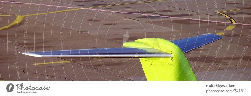 Am Flughafen Flugzeug gelb grau Asphalt Rollfeld Parkplatz Fahrbahnmarkierung Fernweh seitenruder höhenruder heckleitwerk Kreis Linie