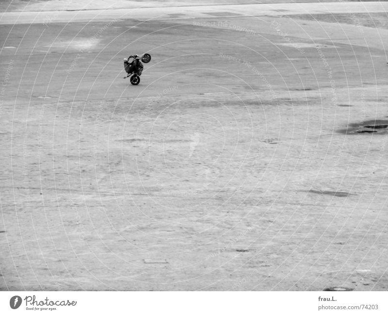 einsames Training Rad Mut üben Motorradfahrer Mann Platz Einsamkeit fahren Sport Spielen Verkehr Mensch kunststück kein beifall keiner sieht zu Künstler