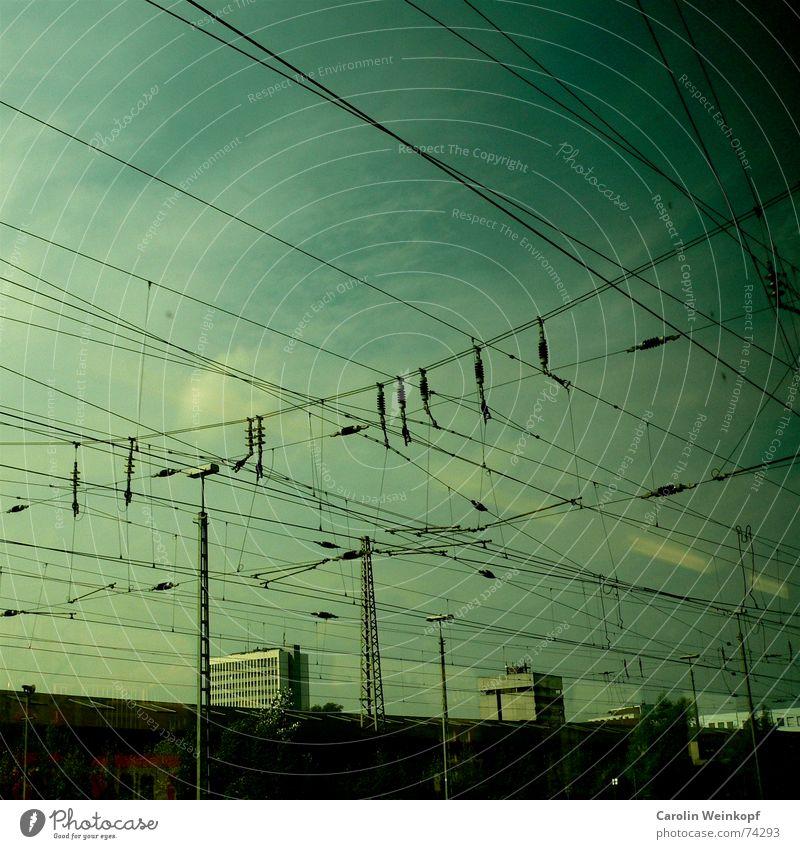 Linientreu. Elektrizität Stadt fahren Ferne Sehnsucht Wolken grün weiß Strommast Abenddämmerung Hochhaus Haus Fluchtpunkt parallel Ruhrgebiet Bahnfahren