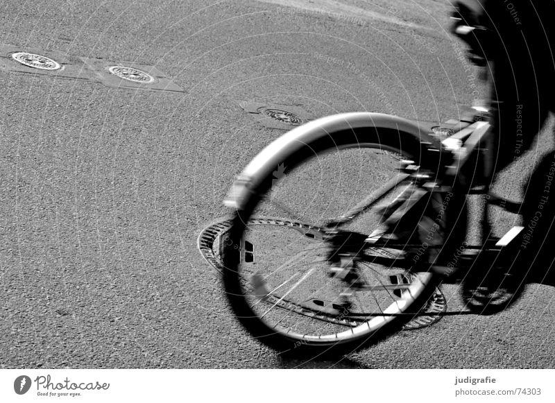 Kanaldeckel - Überrollzustand 1 Asphalt Fahrrad fahren Bewegung Schwung Gully Schacht unterirdisch Gußeisen schwarz weiß Straße Rolle überrollen Dynamik