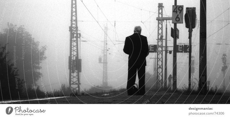 Warten am Bahnhof Bensheim grau Nebel kalt schwarz dunkel weiß Eisenbahn Bahnsteig Mann stehen lesen Anzug Morgen spät Zeit trist Gleise Trauer Verspätung