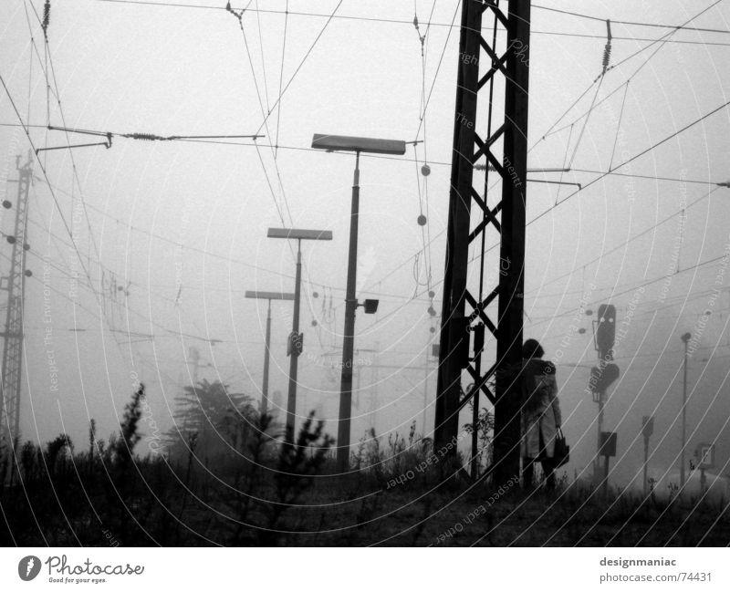 immer noch warten am Bahnsteig Frau weiß schwarz dunkel kalt Gras grau Traurigkeit hell Deutschland Nebel Schilder & Markierungen Zeit Eisenbahn Trauer