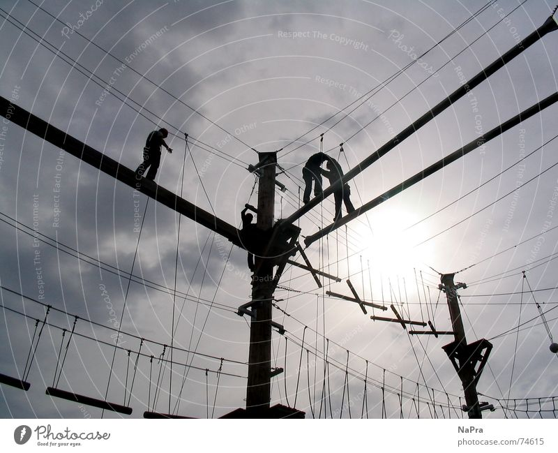 In den Seilen hängen Himmel Sonne Freude Sport Kraft Angst Sicherheit Aktion Elektrizität Klettern Vertrauen Mut Draht Sportler Bergsteiger