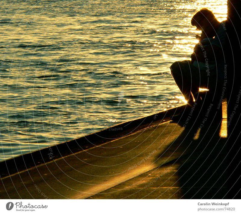 Vater und Sohn Licht Wellen Mann Sonnenuntergang Abenddämmerung Hafen Leben Wasser Schatten Anlegestelle Am Rand Textfreiraum links Mole Gegenlicht Warmes Licht