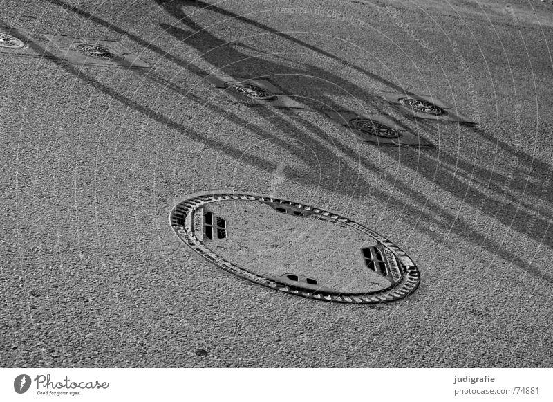 Kanaldeckel - Überrollzustand 2 Asphalt fahren Bewegung Gully Schacht unterirdisch Gußeisen schwarz weiß Straße Schatten Rolle überrollen kontrollschacht
