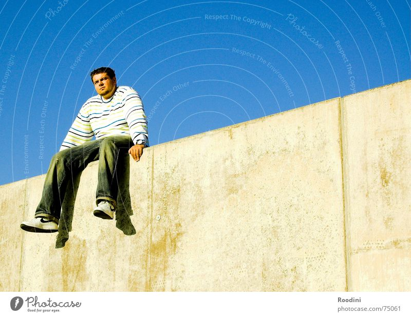 Auf der Mauer, auf der Lauer... Mann Erholung Pause himmelblau Ferne springen Pullover baumeln Sommer Warteraum Wand Grenze beeindruckend Kerl Ecke Streifen