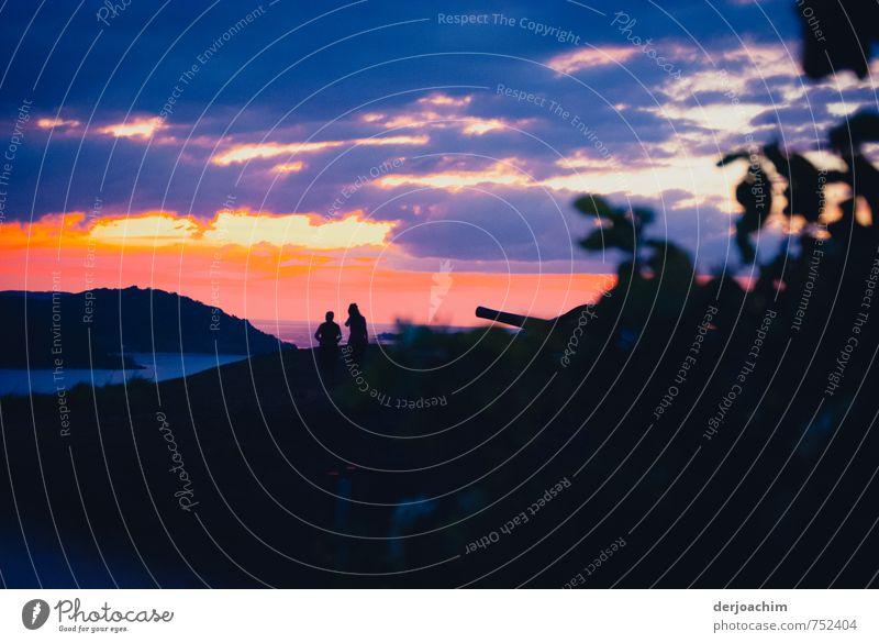 Abenddämmerung auf der Insel. Im Vordergrund sind Büsche. Im Hintergrund zwei Schatten zu sehen. Darüber die Abendsonne mit dunklen Wolken. harmonisch