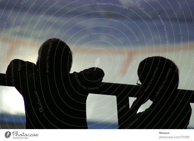Gelangweilte Kinder trist Langeweile Schattenspiel Geländer Silhouette Rückansicht 2 Pause Eisfläche Eisstadion