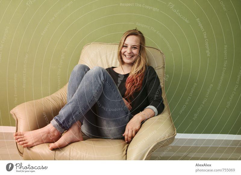 Das lustige Mädchen Sessel Raum Junge Frau Jugendliche Gesicht Fuß 18-30 Jahre Erwachsene Jeanshose Pullover blond langhaarig Lächeln lachen sitzen frech