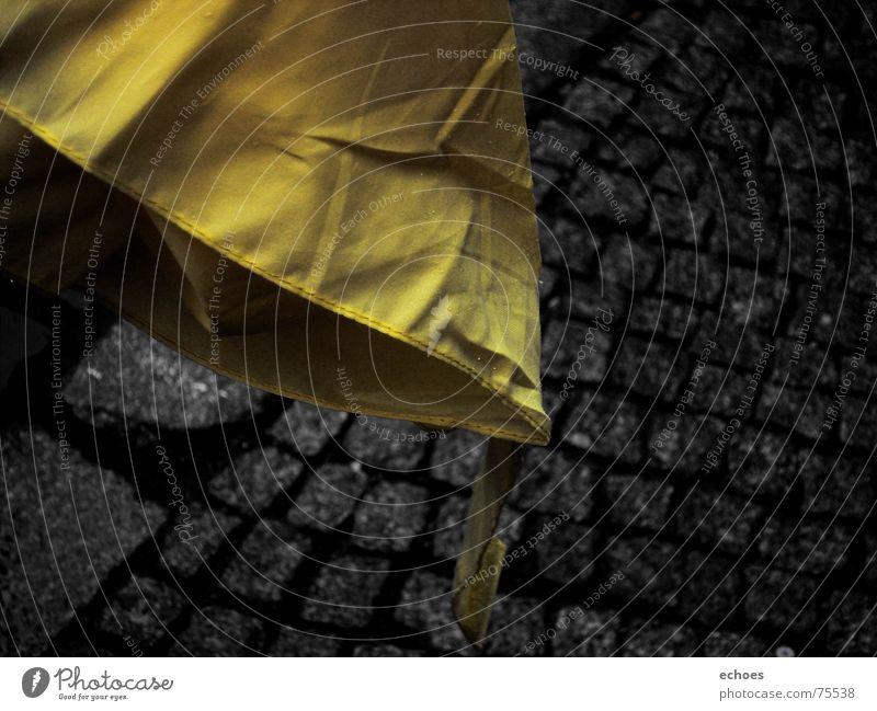 stoned umbrella gelb schwarz Bordsteinkante Bürgersteig Herbst Regen trüb dunkel Grenze kalt nass Regenschirm Stein Kontrast Kopfsteinpflaster Straße hell Falte
