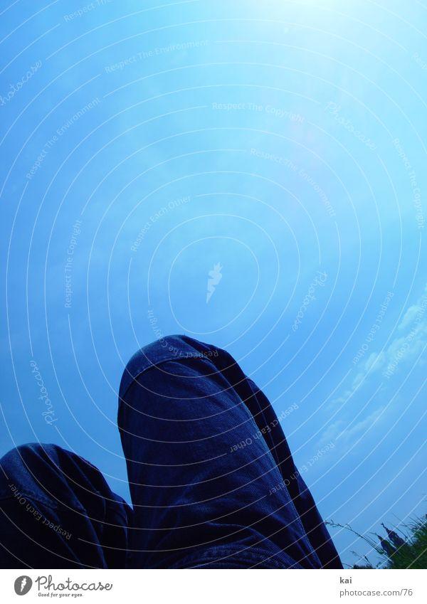 BlaueHoseHoch Knie Wiese Wolken Mensch liegen Beine Jeanshose Jeansstoff Hochformat Froschperspektive Bildausschnitt blau Textfreiraum oben