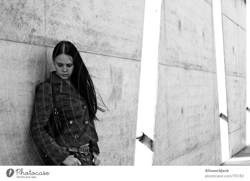 Windschatten Frau Mädchen Wand Beton schwarz weiß Außenaufnahme schwarzhaarig Schüchternheit Einsamkeit trist grau Schwarzweißfoto Haare & Frisuren warten