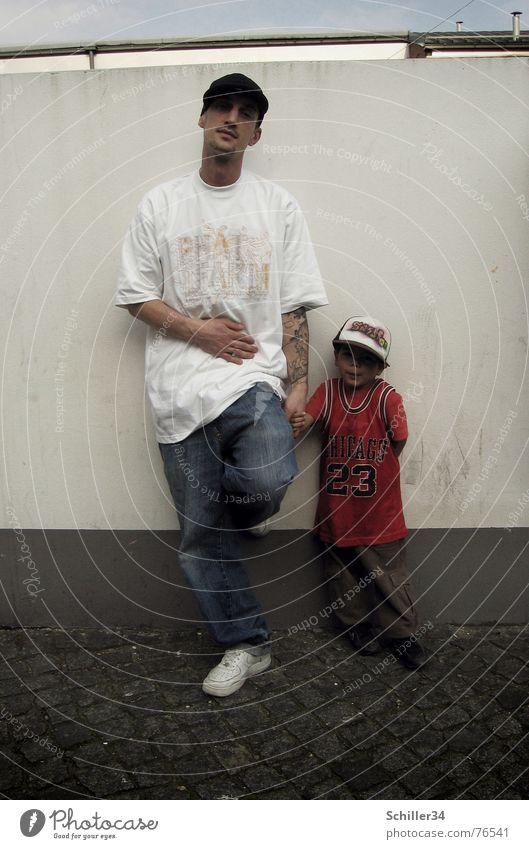 wie der vater so der... Mann Kind Vater Sohn Wand Mauer weiß grau braun T-Shirt rot Baseballmütze Mütze Trikot Hiphop Turnschuh Hose Bart Hand Vertrauen