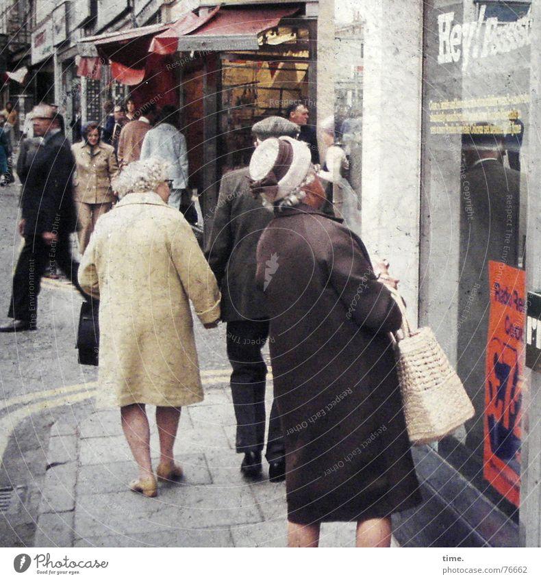 Shopping Hours Mensch alt Straße kaufen lesen Spaziergang Werbung Ladengeschäft Dame Hut Tüte England erstaunt Schaufenster Tasche Hand in Hand