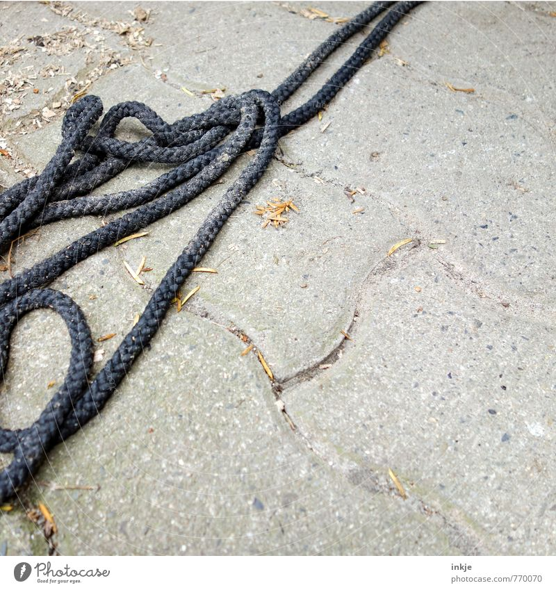 Kabelsalat Umwelt Menschenleer Terrasse Pflasterweg Pflastersteine Bodenbelag Seil Knoten alt dreckig lang grau schwarz chaotisch durcheinander Schlaufe Müll