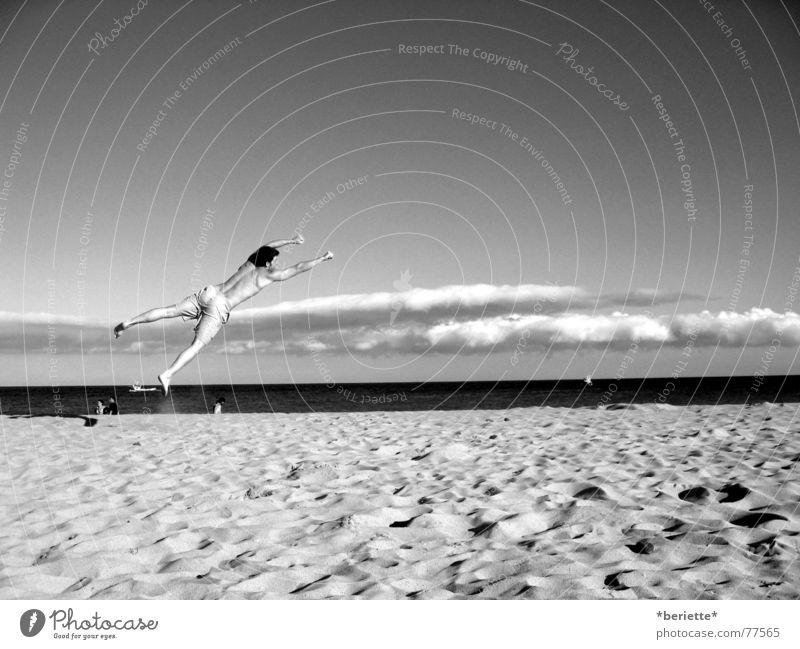 Freiheit 2 Mann Badehose springen Strand Physik Sommer Meer nass salzig Wolken drehen toben schwarz weiß Muskulatur Wärme Himmel blau Sand Freude lustig