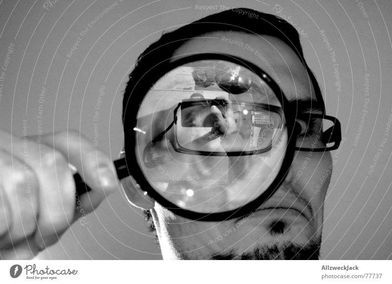 Suchbild untersuchen Suche schwarz Wut böse Brille Selbstportrait Innenaufnahme Blick Lupe käferperspektive Schreibtisch Schwarzweißfoto vergrößert