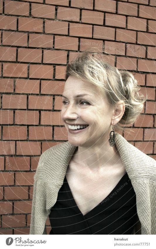 lachend Frau 50 Backstein Wand blond Zopf Zähne