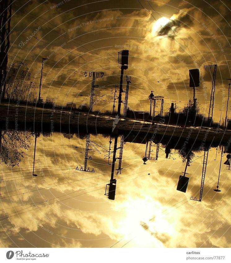 pfÜTzE 2 Wasser Sonne Wolken dunkel Herbst Eisenbahn Elektrizität bedrohlich Gleise Bahnhof Strommast Pfütze Leitung dramatisch Signal Oberleitung