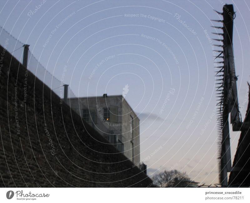L'heure bleu Himmel dunkel Mauer Gebäude trist Zaun Barriere Justizvollzugsanstalt Stacheldraht