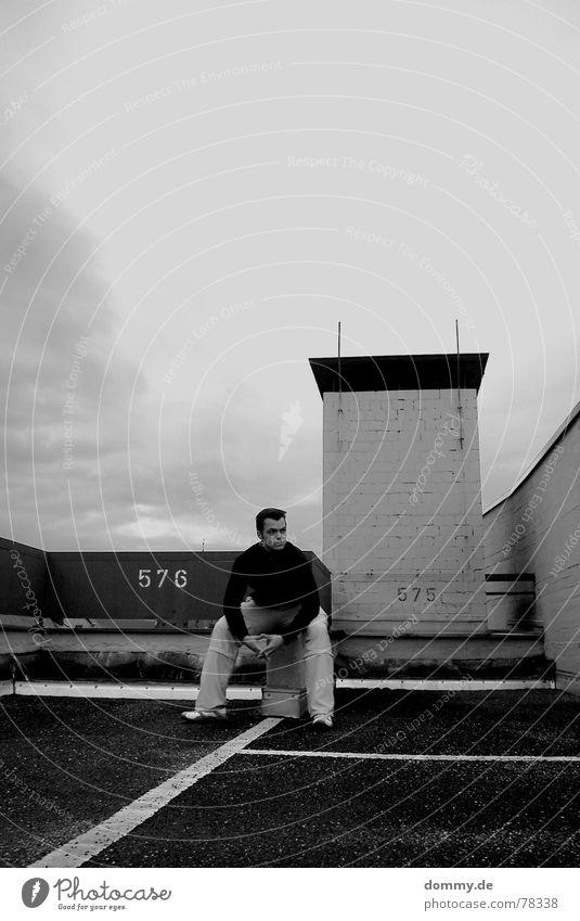 576-575 Mann weiß schwarz Haus Wolken dunkel kalt Herbst grau Stein Mauer Park Regen Schuhe Linie nass