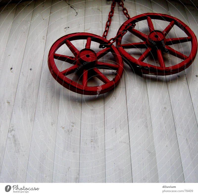 rote räder Holz Wand weiß Wagen hängen Kette alt Lack Kontrast Schatten