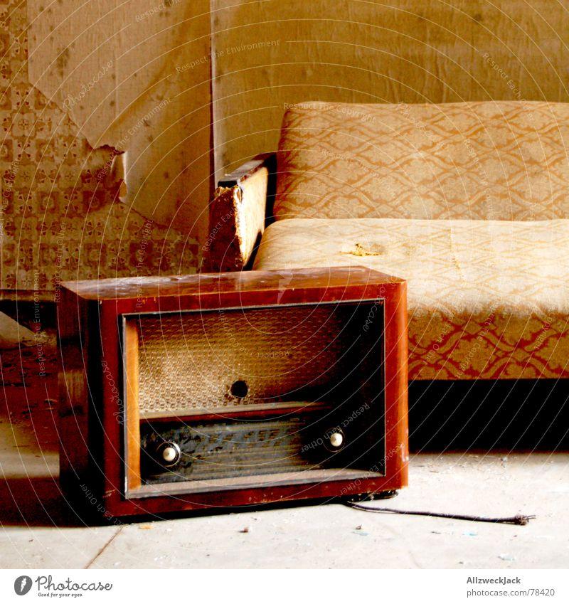 Wohlfühlecke Radiogerät Schlafsofa Mittelwelle Sofa Liege Osten Siebziger Jahre Tapete Fetzen Staub dreckig Stillleben unordentlich tapetenfragment alt