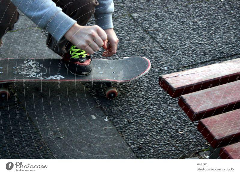 VOR DEM SPRUNG fahren springen hüpfen Beginn Schuhbänder Knie London Underground Skateboarding gebeugt Erwartung Nervosität aufregend Spannung Asphalt grün Hand