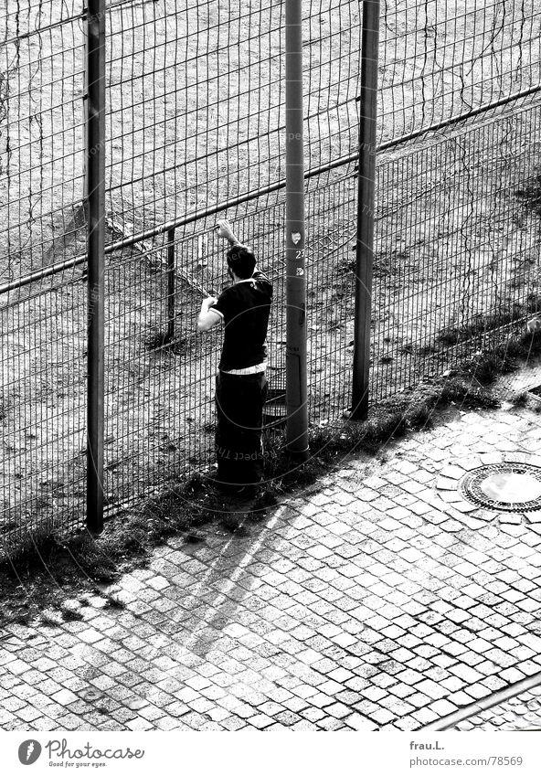 Zaungast Mensch Mann Hand Einsamkeit Spielen Junger Mann beobachten Asphalt festhalten Bart Straßenbelag gefangen Pflastersteine Fußballplatz Außenseiter