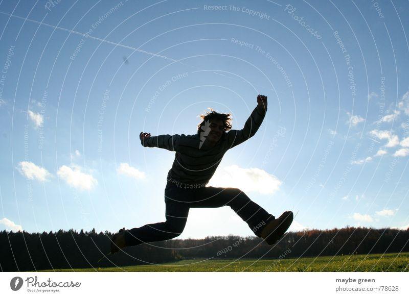 Sprung in den Herbst Mann Jugendliche grün blau Freude Wolken Wald springen Frühling Beine Arme