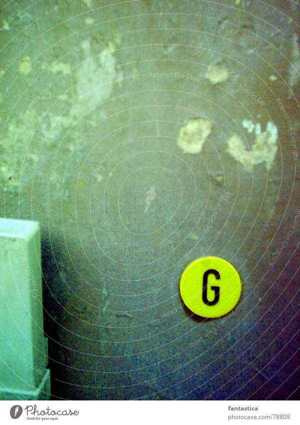 Der G-Punkt Straßenrand Buchstaben grau grün gelb Wand Morgen Schriftzeichen Zeichen Gas