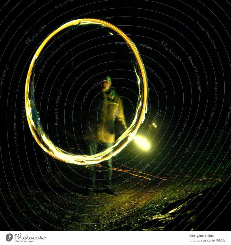 Spiel mit dem Feuer sprühen o rund dunkel schwarz gelb grün Nacht brennen Schwung unterwegs Mann Jacke kalt heiß gefährlich Suche Mantel Licht Vergangenheit