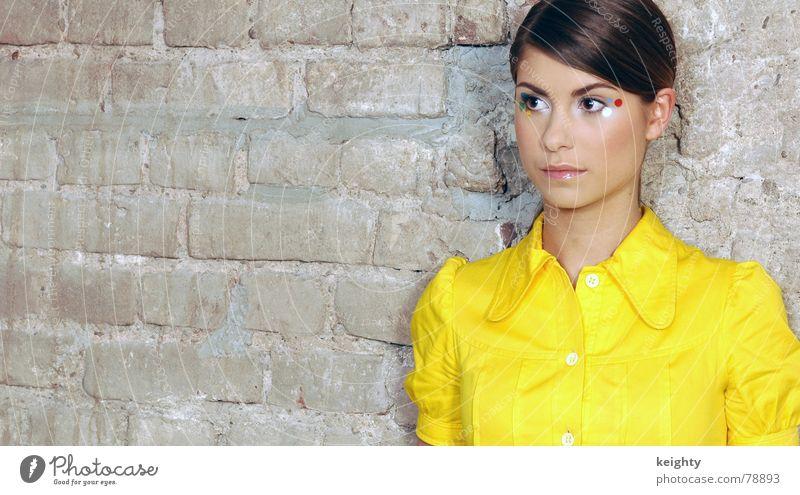Girls @ the wall Frau Gesicht gelb feminin Haare & Frisuren Mauer braun Mund Nase stehen Kleid Punkt Backstein Schminke Knöpfe