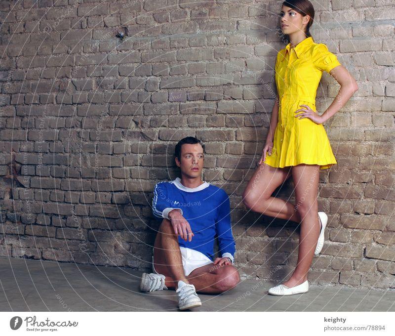 bored Frau Mann blau gelb Mauer Schuhe sitzen T-Shirt stehen Bodenbelag Kleid Hose Konzentration Turnschuh abstützen