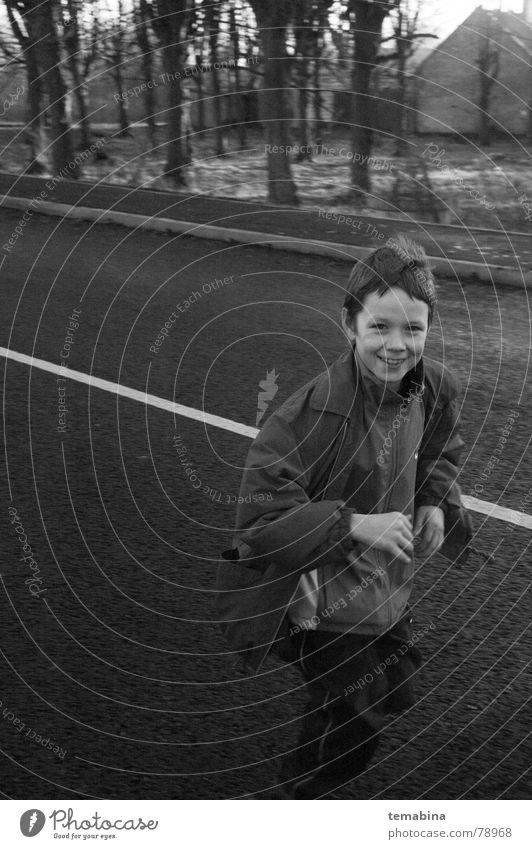 Boy Running Monochrom Riga grinsen Freude running suburb smiling white street Schwarzweißfoto