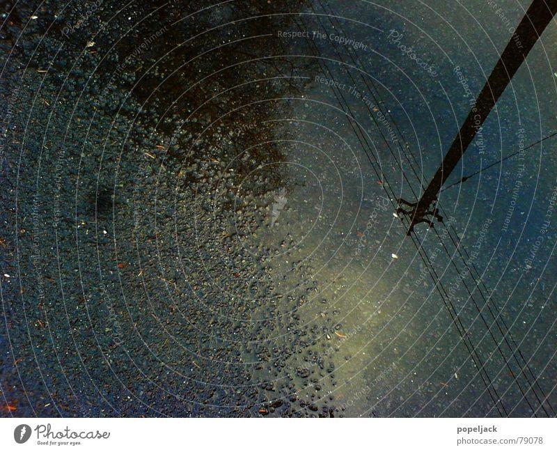 Schau auch mal nach unten Elektrizität Pfütze Asphalt Herbst nass feucht Glätte Strommast Leitung Wasser Straße Wetter Regen Wassertropfen rau