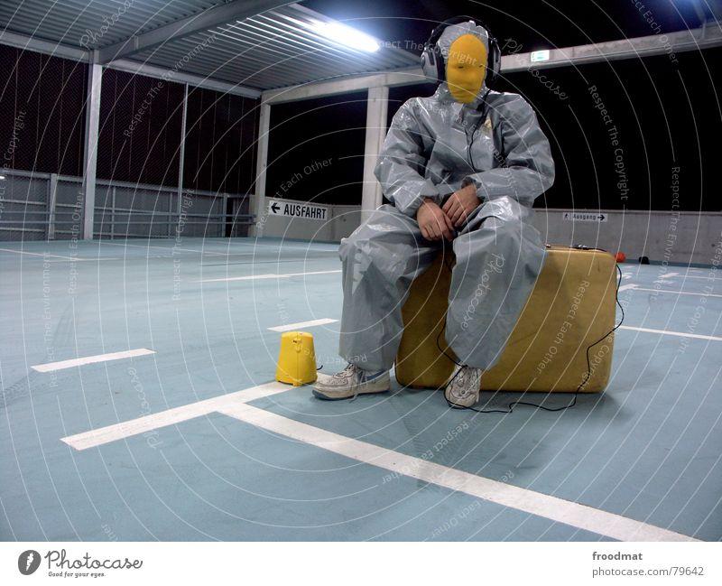 grau™ - sitzt auf gepacktem koffer Parkhaus gelb grau-gelb Anzug Gummi Kunst dumm sinnlos ungefährlich verrückt lustig Freude Taschenlampe Kopfhörer