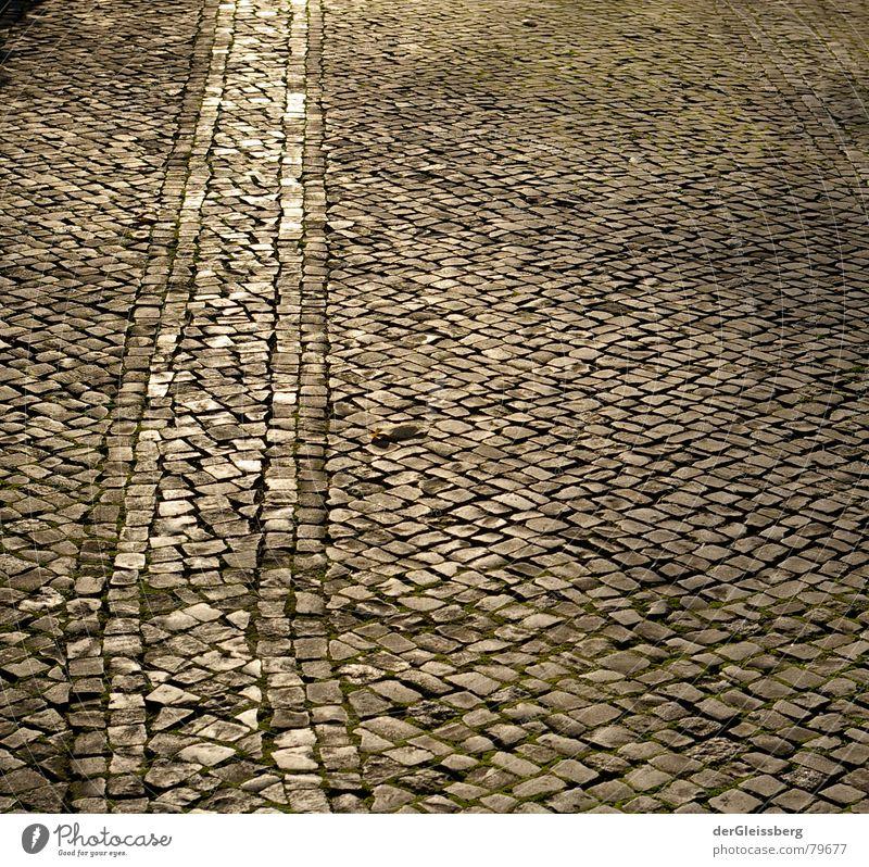 geh den Weg der Sonne Gold Furche richtig Verlässlichkeit Kopfsteinpflaster erleuchten dunkel beruhigend kalt Spuren gelb grau Fahrbahn grell Stadt Straßenbelag