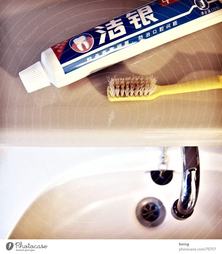 stehts bemüht gepflegt und gebildet zu wirken Schriftzeichen Bildausschnitt Anschnitt Abfluss Waschbecken Tube Objektfotografie Zahnbürste Zahncreme Zahnpflege Vor hellem Hintergrund