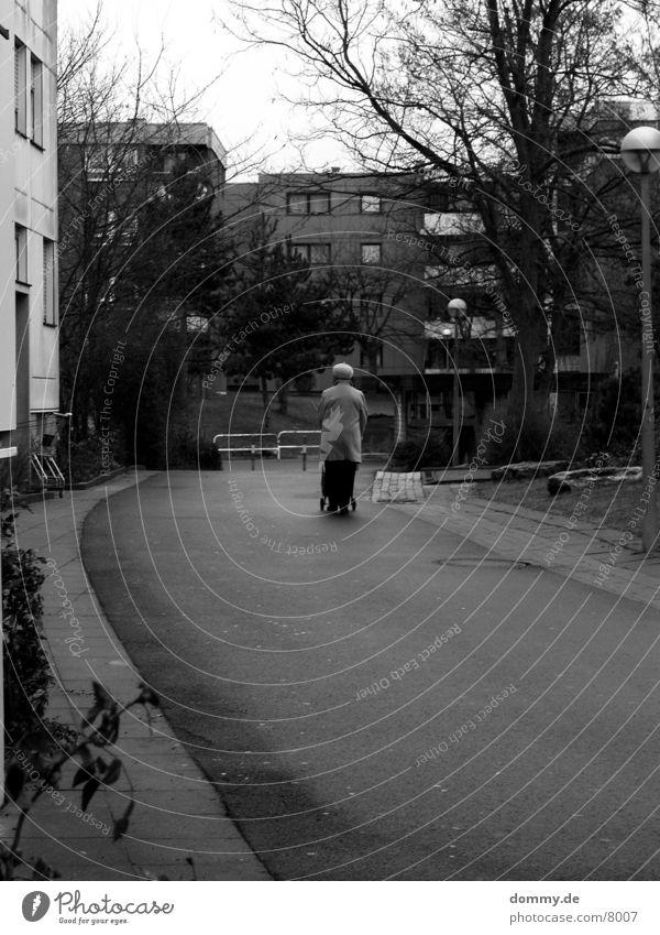 Einsamkeit macht einsam Frau alt Winter Spaziergang Fußweg Weiblicher Senior Gehhilfe Wohngebiet Rollator