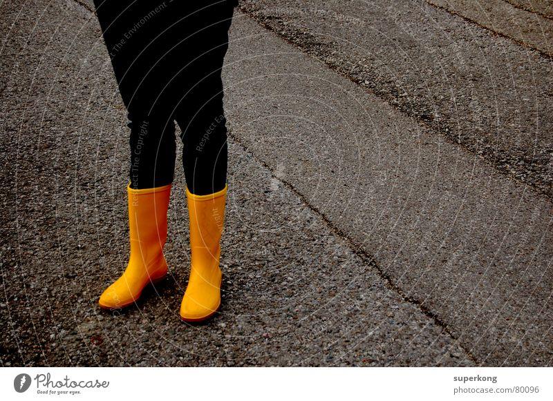 015 Gummistiefel gelb Beton Winter Herbst nass Herbstbeginn Regen Straßenbelag Fernstraße feucht gelbe stiefel blau jean Schutzdach humid ausfallstraße