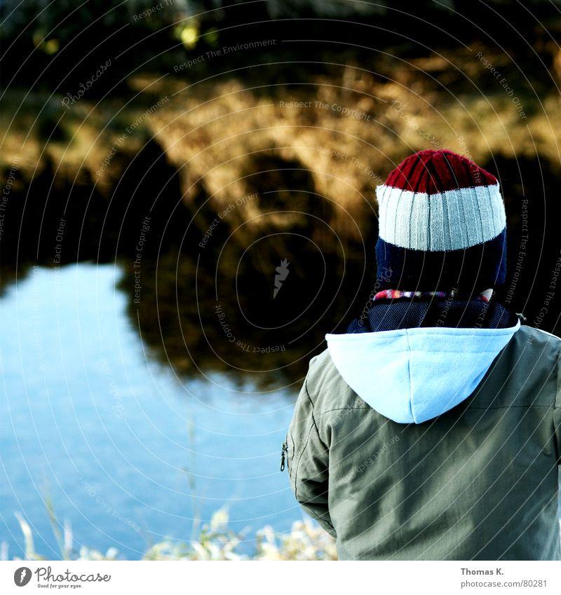 Zeit (oder: Ufer halten das Wasser) Kind Natur Wasser Einsamkeit Junge Herbst Gras Traurigkeit Küste Fluss Jacke Mütze Kleinkind Bach Kapuze Deich
