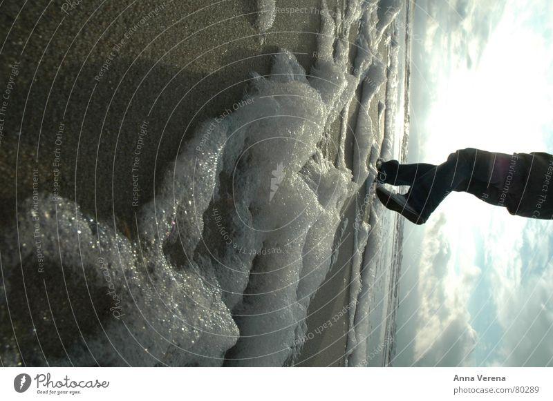 Nordseeschaum Schaum Meer Sylt Küste Winter Jacke Schuhsohle Froschperspektive Wolken graue Wolken Ebbe strahlend kalt Strand Sand Sonne Beine Fuß Chucks