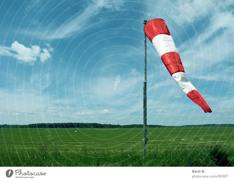 Wind im Sack Windsack Schliere Windrichtung rot Wolken himmelblau gestreift Luft Wiese Flugplatz Gras Fahnenmast hängen grün luftig frisch Wolkenband Luftraum